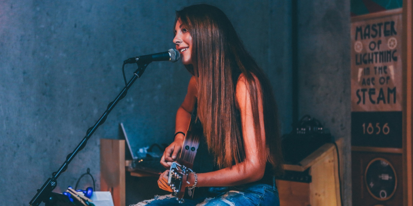 Young female vocalist performs with her guitar.
