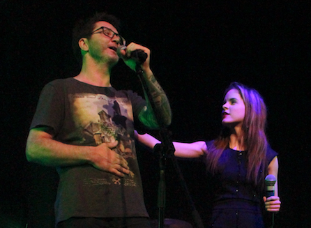 Male vocalist is encouraged by his vocal coach during a performance.