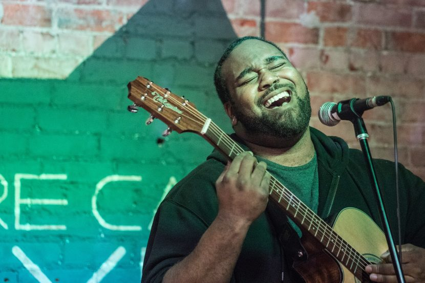 Male vocalist sings at an open mic night with his guitar.
