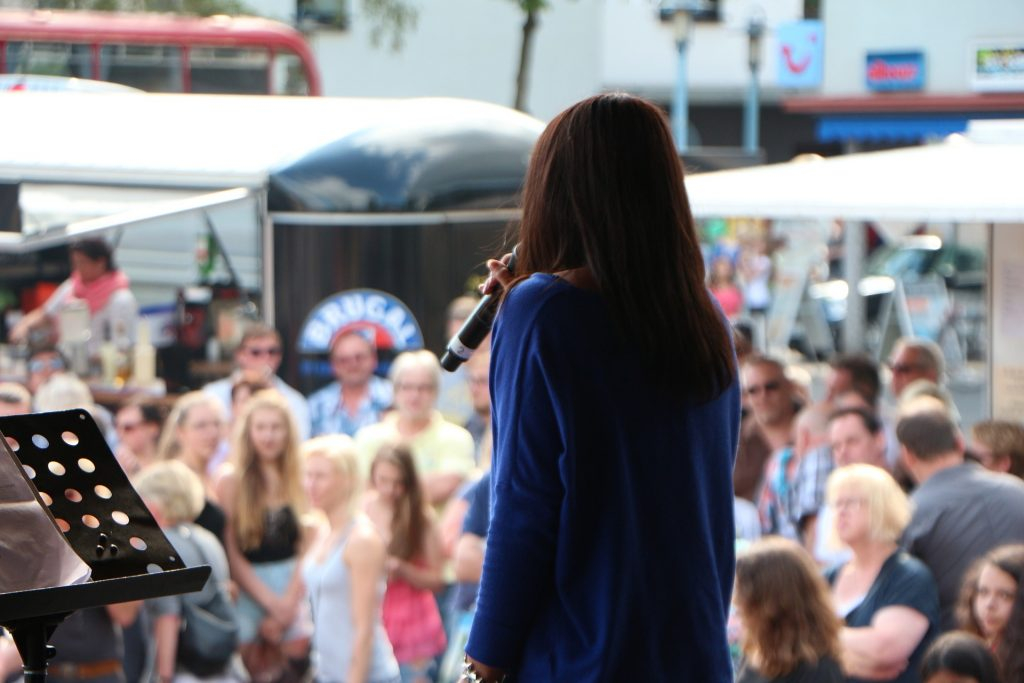 Female vocalist sings in front of a crowd at a music festival with average posture.