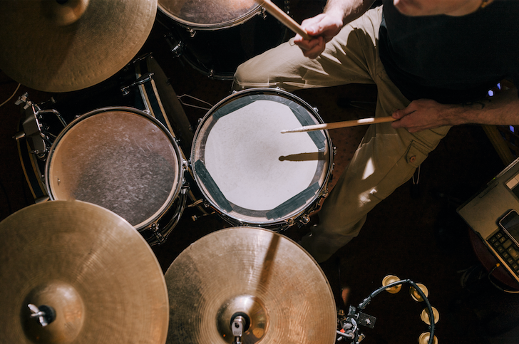 Male drummer performs essential rudiments on his drum kit.