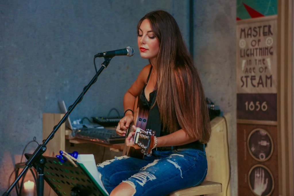 Female performer sings and plays guitar at a cafe.